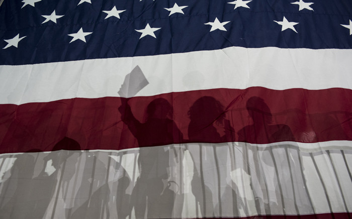 People silhouetted in a large American flag at a rally following Super Tuesday on 2 March 2016 in New York City. Picture: AFP.