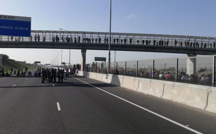 Police monitor protesters along the R300 near Kuils River on 22 July 2020. Picture: @SAPoliceService/Twitter