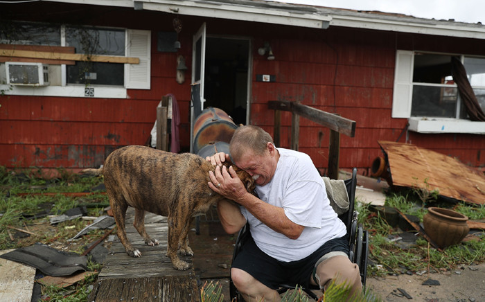 """Steve Culver cries with his dog Otis as he talks about what he said was the, """"most terrifying event in his life,"""" when Hurricane Harvey blew in and destroyed most of his home while he and his wife took shelter there on 26 August, 2017 in Rockport, Texas. Picture: AFP."""