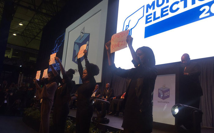 """Four female EFF members holding placards in front of the stage as President Jacob Zuma delivers his address at the IEC national results centre in Pretoria. The placards refer to the woman named """"Khwezi"""" who accused Zuma of rape in 2005. Picture: Masa Kekana/EWN."""