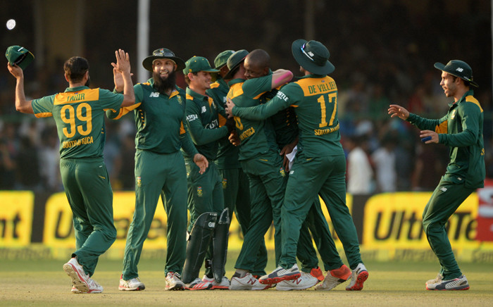 South Africa's Hashim Amla (2L) celebrates with teammates after their victory in the first one day international (ODI) cricket match between India and South Africa at Green Park Stadium in Kanpur on October 11, 2015. Picture: AFP.