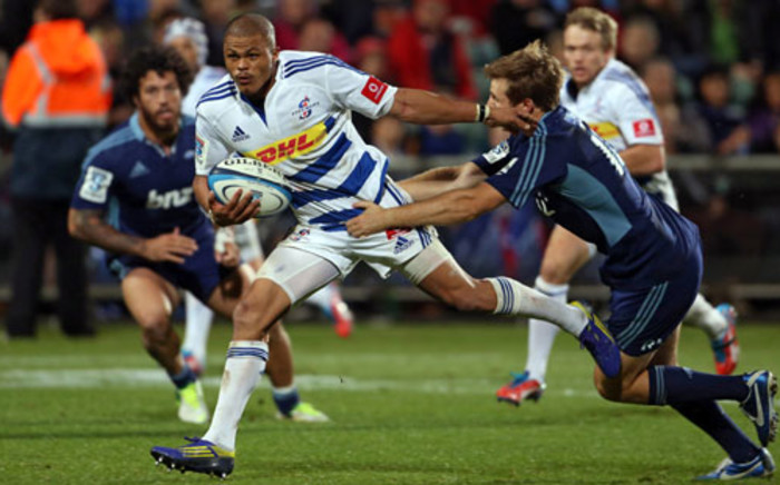 Stormers players Juan De Jongh (C) fends off the tackle of Auckland Blues player Chris Noakes.  Picture: AFP.