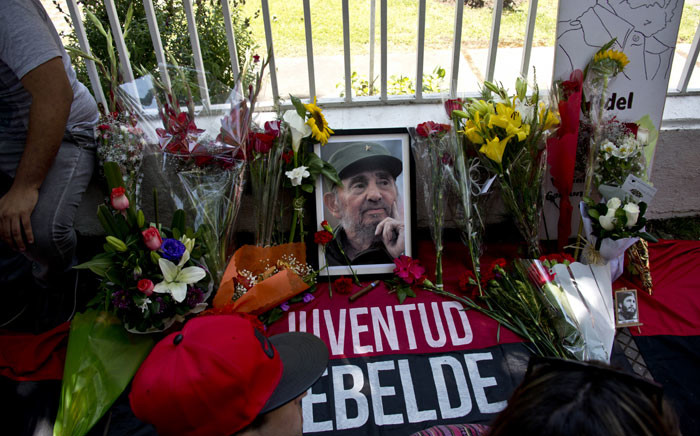 A portrait of Cuban historic revolutionary leader Fidel Castro is surrounded by flowers as people gather outside the Cuban embassy in Santiago on 26 November 2016. Picture:AFP.