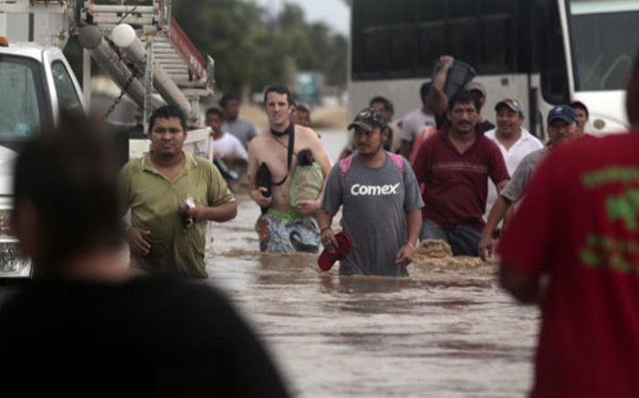 Residents and tourists wade through a flooded street in Acapulco, Guerrero state, Mexico, after heavy rains hit the area on 16 September 2013. Picture: AFP