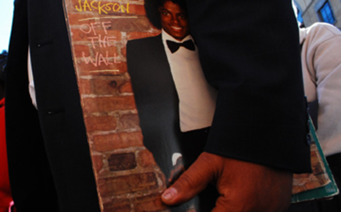 A Michael Jackson fan holds a copy of one of his records. Picture: Taurai Maduna/Eyewitness News