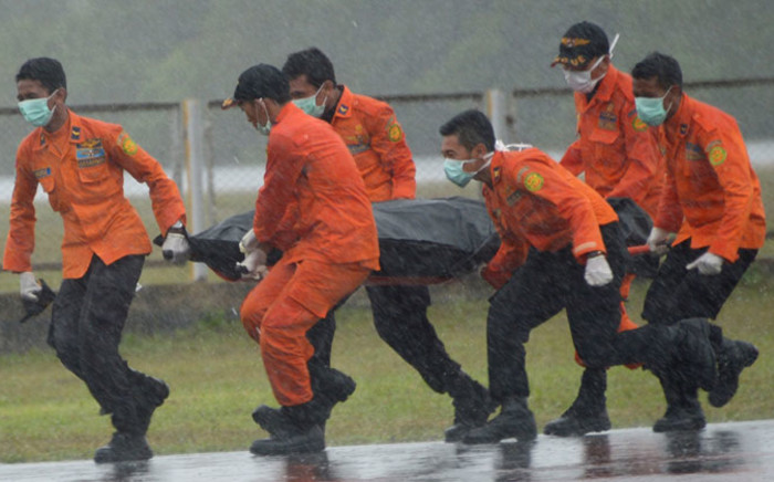 Members of an Indonesian search and rescue team transport the body of a victim from AirAsia flight QZ8501 recovered from the Java Sea in the rain at Pangkalan Bun in Central Kalimantan on 1 January, 2015. Picture: AFP.