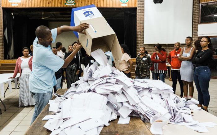 An Independent Electoral Officer (IEC) opens a ballot box as counting begins at the Addington Primary School after voting ended at the sixth national general elections in Durban, on 8 May 2019. Picture: AFP