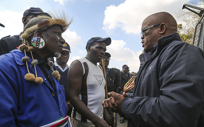 Keith Khoza from the Gauteng Human Settlements department speaks to hostel residents during demonstrations calling for the reinstatement of sanitation and maintenance services in Johannesburg hostels. Picture: Reinart Toerien/EWN