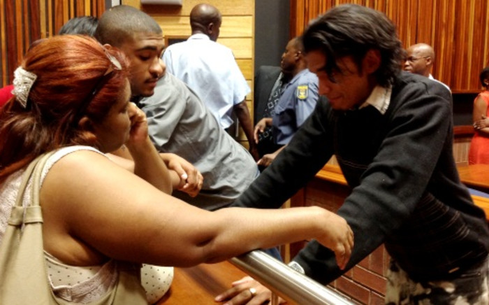 Lindon Wagner (R) speaks to his mother and brother after being found guilty of murdering Kirsty Theologo on 7 November 2013. Picture: Govan Whittles/EWN
