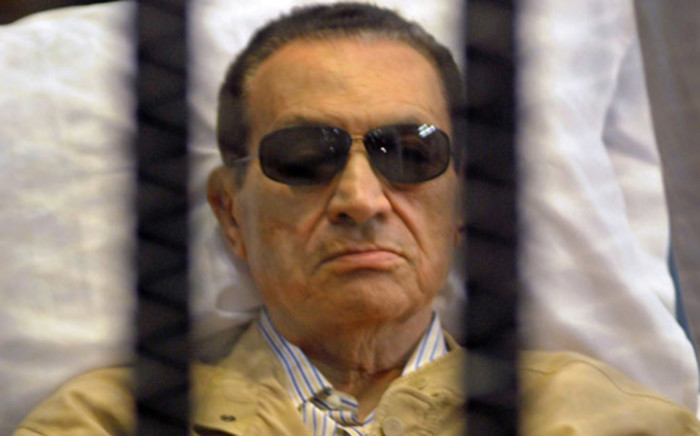 Ousted Egyptian president Hosni Mubarak sits inside a cage in a courtroom. Picture: AFP.