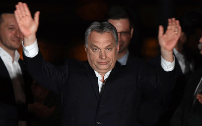 Hungarian Prime Minister Viktor Orban celebrates on podium on the bank of the Danube River after winning the parliamentary election with members of his FIDESZ party on 8 April, 2018 in Budapest. Picture: AFP.