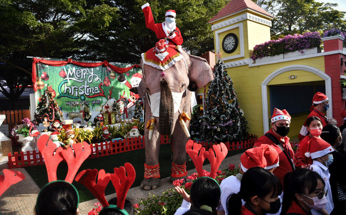 An elephant from the Ayutthaya Elephant Palace, dressed in a Santa Claus costume and wearing a face mask, is greeted by students during an event to hand out face masks outside the Jirasat Wittaya School in the central Thai province of Ayutthaya on December 23, 2020. Picture: AFP.