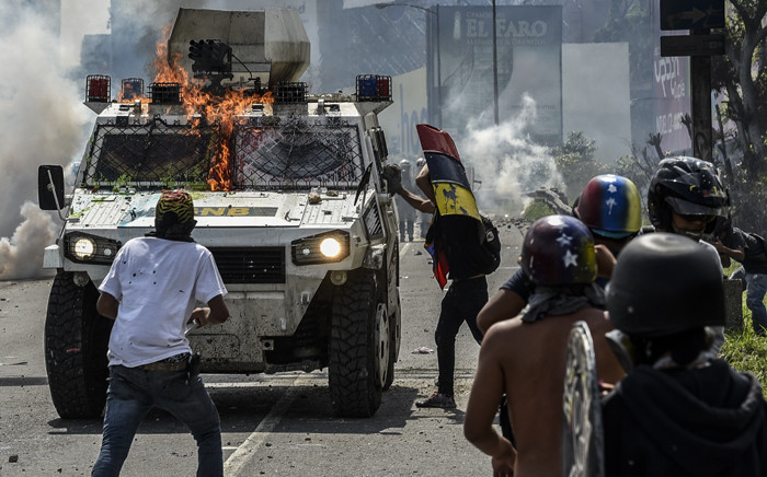 """Opposition activists clash with riot police during a protest against President Nicolas Maduro in Caracas, on May 10, 2017. Venezuelan protesters hit the streets on Wednesday armed with """"Poopootov cocktails,"""" jars filled with excrement which they vowed to hurl at police as a wave of anti-government demonstrations turned dirty. Picture: AFP"""