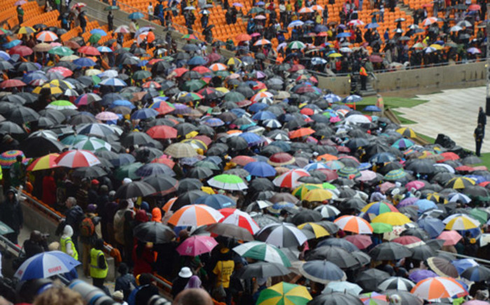 """""""People came with umbrellas at FNB Stadium as the rain poured down during Nelson Mandela memorial on 10 December 2013. Picture: Christa Van der Walt/EWN."""