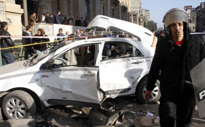 An Egyptian policeman walks in front of a damaged car outside the Museum of Islamic Art following a car bomb explosion outside the Cairo police headquarters situated near the museum in the Egyptian capital on 24 January. Picture: AFP.