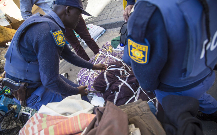 FILE: Police search suspicious bags while Red Ants evict residents of a block of flats on Harrison Street in Jeppestown. Picture: Thomas Holder/EWN