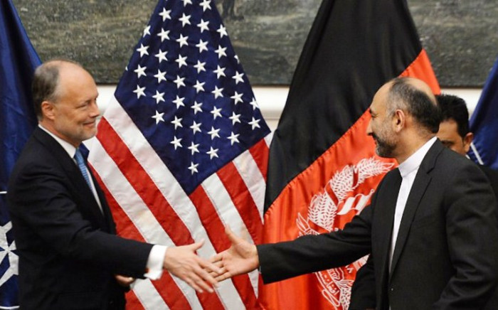 Afghan National Security Adviser Hanif Atmar (R) shakes hands with US Ambassador to Afghanistan James Cunningham (L) before they sign documents to allow some US troops to stay in Afghanistan at the Presidential Palace in Kabul on 30 September 2014. Picture: AFP.