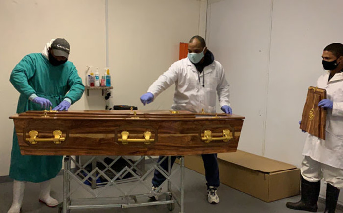 Undertakers at the People's Choice Funerals and Mortuary prepare a coffin for burial. Picture: Kaylynn Palm/EWN
