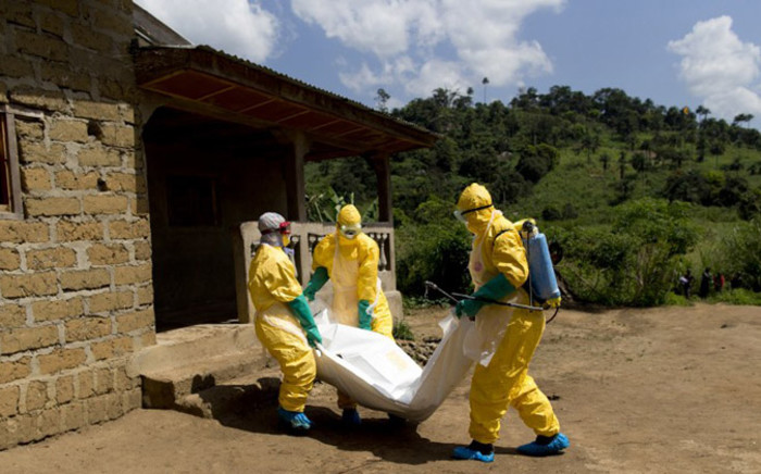 FILE: Guinean Red Cross workers wearing protective suits carry the corpse of a victim of Ebola in Macenta on 21 November 2014. AFP