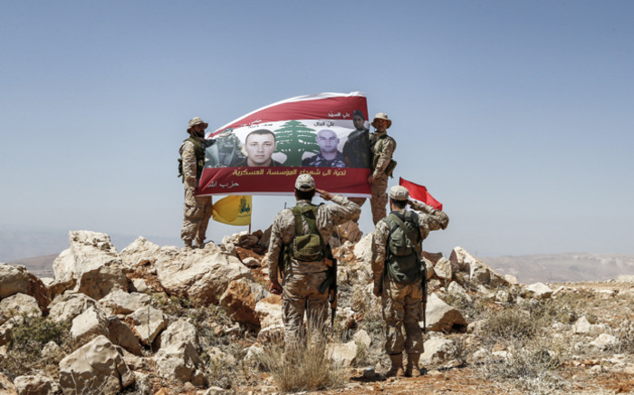 Fighters from the Lebanese Shi'ite Hezbollah movement raise up and salute a banner in a mountainous area around the Lebanese border town of Arsal during a tour guided by the group on 26 July 2017, showing the photos of members of the Lebanese Army killed fighting militant groups along the eastern border with war-ravaged Syria. Picture: AFP.