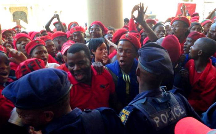 Police try to stop members of the EFF from storming the Gauteng Provincial Legislature on 22 July 2014. Picture: Masego Rahlaga/EWN.