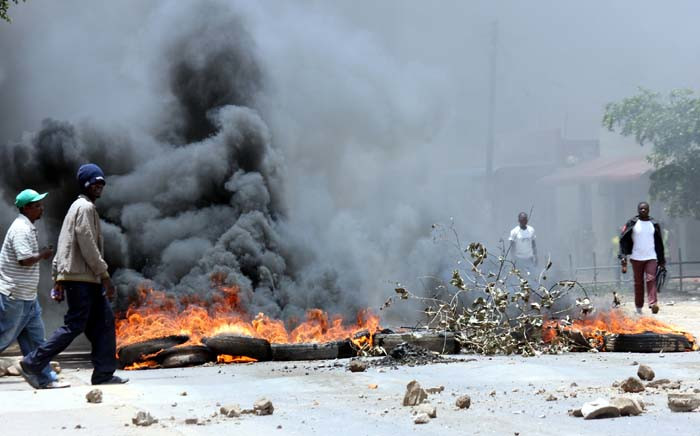 Resident of Lusaka's Kanyama Township walk past a burning barricade of tyres during clashes with protesters demonstrating against a curfew imposed by the government in the wake of a cholera outbreak. Picture: AFP.