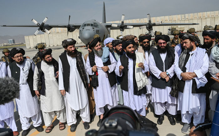 Taliban spokesperson Zabihullah Mujahid (C, with shawl) speaks to the media at the airport in Kabul on 31 August 2021. The Taliban joyously fired guns into the air and offered words of reconciliation as they celebrated defeating the United States and returning to power after two decades of war that devastated Afghanistan. Picture: Wakil Kohsar/AFP