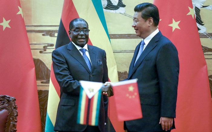 """Zimbabwean President Robert Mugabe (L) and his Chinese counterpart Xi Jinping shake hands during a signing ceremony at the Great Hall of the People in Beijing on August 25, 2014. China's President Xi hailed Mugabe -- a pariah in the West -- as a renowned African liberation leader and an """"old friend"""" of the Chinese people. Picture: AFP."""