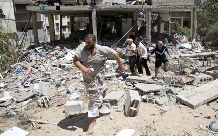FILE: Palestinian medics help evacuate a survivor after an Israeli airstrike on his home in Gaza City on 27 July, 2014