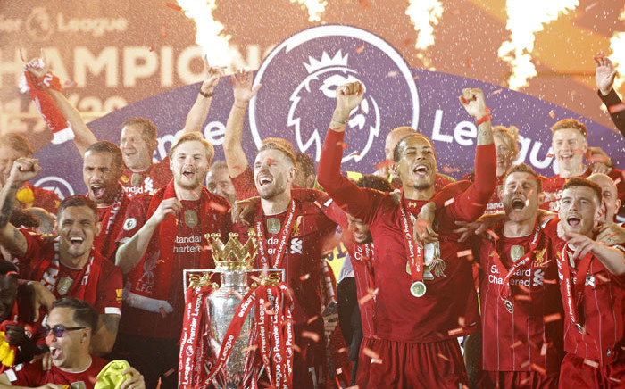 Liverpool captain Jordan Henderson (C), defender Virgil van Dijk (3R), midfielder James Milner (2R) and defender Andrew Robertson (R) pose with the Premier League trophy during the presentation following the English Premier League football match between Liverpool and Chelsea at Anfield in Liverpool, north west England on 22 July 2020. Picture: AFP