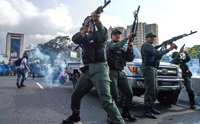 Members of the Bolivarian National Guard who joined Venezuelan opposition leader and self-proclaimed acting president Juan Guaido fire into the air to repel forces loyal to President Nicolas Maduro who arrived to disperse a demonstration near La Carlota military base in Caracas on 30 April 2019. Picture: AFP