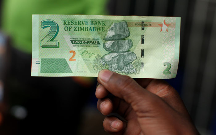 FILE: A man holds a bond note released by the Reserve Bank of Zimbabwe in Harare central business centre. Picture: AFP