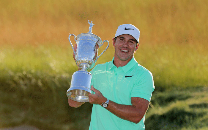 Brooks Koepka of the United States poses with the US Open trophy after his victory at the 2017 US Open at Erin Hills on 18 June 2017. Picture: AFP
