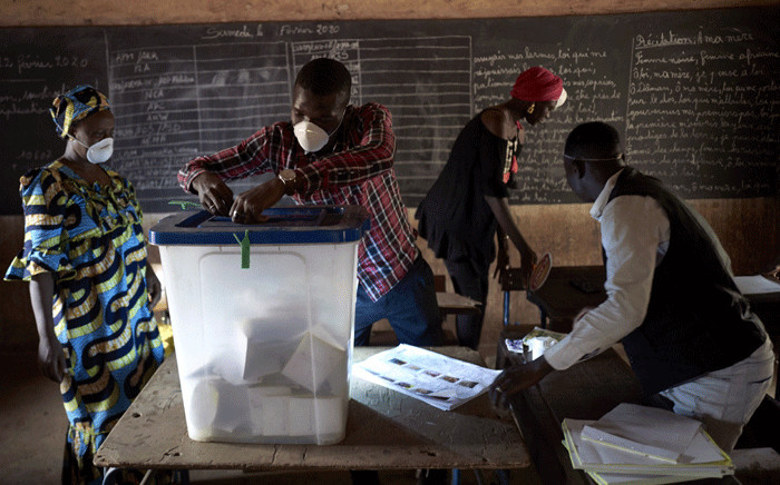 An electoral official wearing a mask as a preventive measure against the spread of the COVID-19, removes the seals of a ballot box at a polling station in Bamako on March 29, 2020. Picture: AFP.