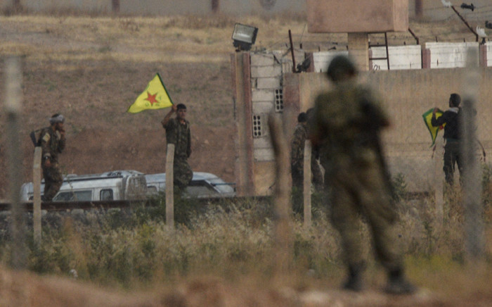 Kurdish People's Protection Units (YPG) fighters hold their movement€'s flag while a Turkish soldier looks at them near the Akcakale crossing gate in Sanliurfa province in June 2015. Picture: AFP.
