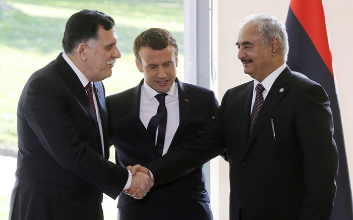 French President Emmanuel Macron (C) looks on as Libyan PM Fayez al-Sarraj (L) shakes hands with General Khalifa Haftar (R), commander in the Libyan National Army after talks aimed at easing tensions in Libya. Picture: AFP.