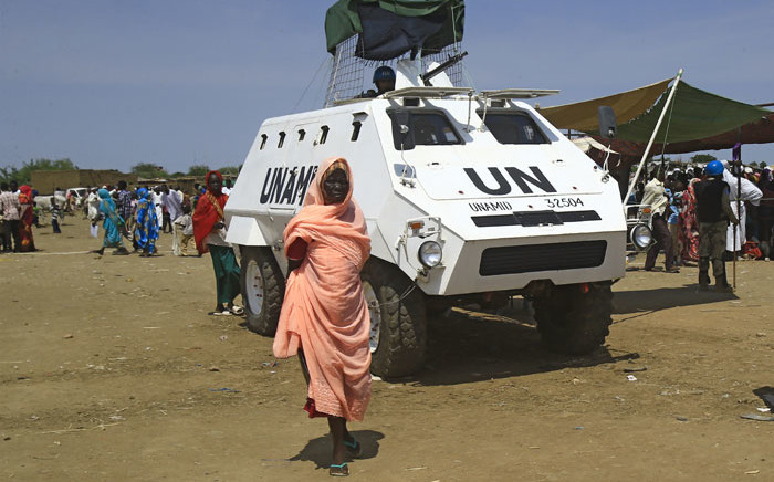 FILE: A displaced Sudanese woman walks past an UN-African Union mission to Darfur (UNAMID) vehicle at the Kalma camp for internally displaced people in Darfur's state capital Niyala on 9 October 2019. Picture: AFP