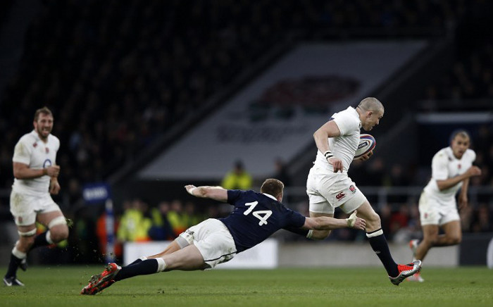 Scotland wing Doug Fife (C) dives to attempt to tackle England full back Mike Brown (R) during the Six Nations international rugby union match between England and Scotland at Twickenham Stadium, south west of London on 14 March, 2015. England won the game 25 - 13. Picture: AFP