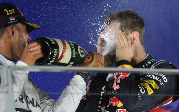 Mercedes driver Lewis Hamilton of Britain (L) sprays the bottle of champagne over Red Bull Racing driver Sebastian Vettel of Germany (R) on the podium after winning the Formula One Singapore Grand Prix at the Marina Bay street circuit on 21 September, 2014. Picture: AFP.