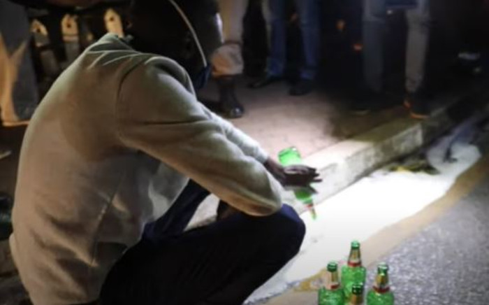 A man in Soweto pours the alcohol he had in his possession during a police operation on Saturday, 06 June 2020, on the  first weekend since the level 3 lockdown which permits the sale of alcohol. Picture: EWN