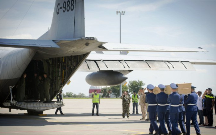 Ukrainian soldiers carry coffins with the remains of victims of the Malaysia Airlines flight MH17 crash to a military plane during a ceremony at the airport of Kharkiv, Ukraine, on 23 July 2014. Picture: AFP.