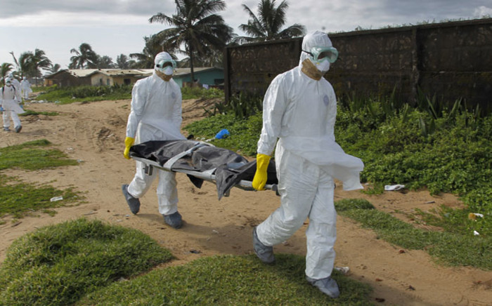 Liberian health workers in a burial squad carrying the body of an Ebola victim in Monrovia in September 2014. Picture: EPA.