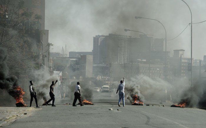 Protesters gesture towards police officers (not seen) as they burn tyres in Jeppestown, Johannesburg, on 11 July 2021. Picture: Luca Sola/AFP