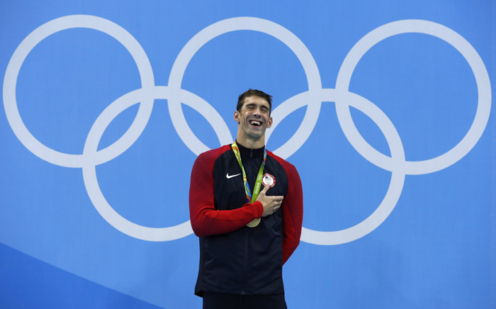 USA's Michael Phelps laughs on the podium with his gold medal after he won the Men's 200m Butterfly Final during the swimming event at the Rio 2016 Olympic Games at the Olympic Aquatics Stadium in Rio de Janeiro on 9 August, 2016. Picture: AFP.