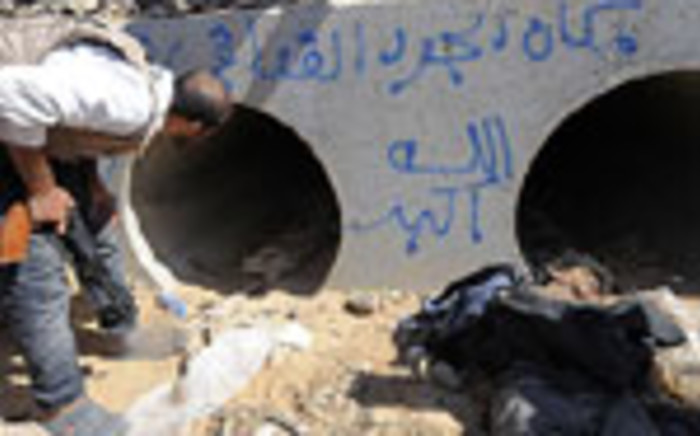 An NTC fighter looks through the concrete pipe where deposed Libyan leader Muammar Gaddafi was allegedly shot and captured during a gun battle on 20 October 2011 in Sirte. Picture: AFP