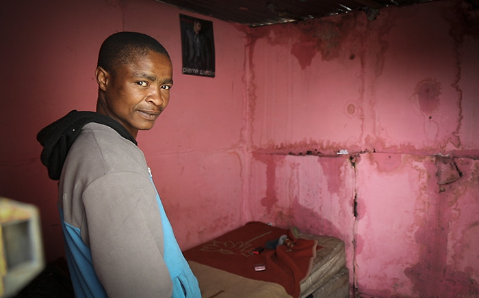 A Khayelitsha resident stands in his water-damaged home on 24 July 2015 after heavy rains caused misery for informal settlement residents. Picture: Aletta Gardner/EWN