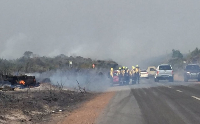 Firefighters attend to the blaze along Red Hill Road. Picture: Kevin Brandt/EWN.
