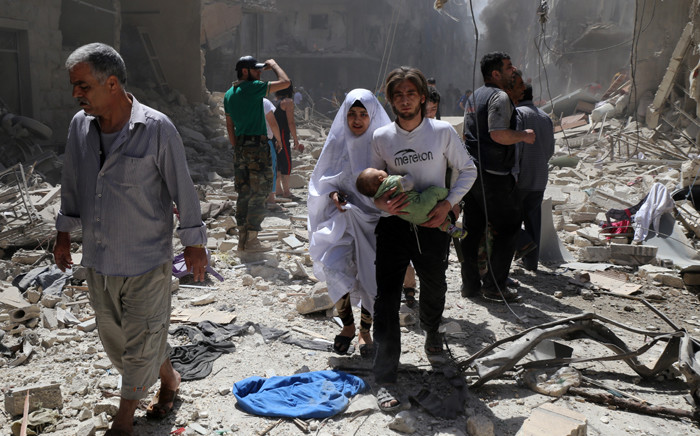 FILE: A Syrian family walks amid the rubble of destroyed buildings following a reported airstrike on the northern Syrian city of Aleppo. Picture: AFP.