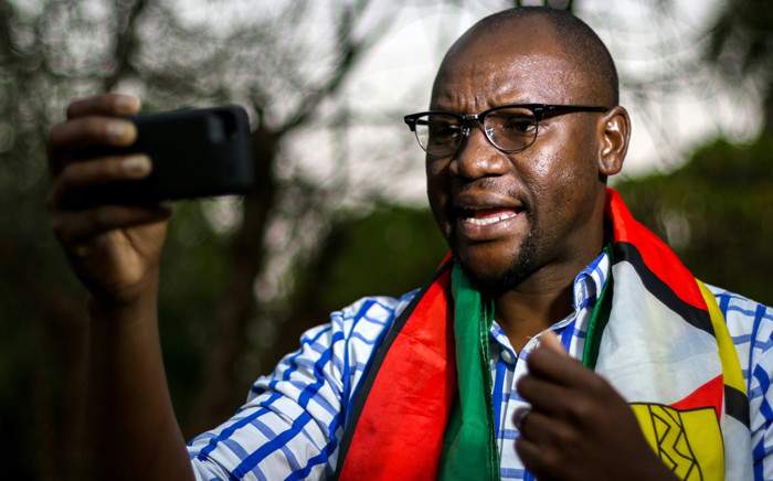 """This file photo taken on 19 May 2016 shows Zimbabwean cleric Evan Mawarire, wrapped in the Zimbabwean national flag, recording an installment of his #ThisFlag video series. Picture: AFP."