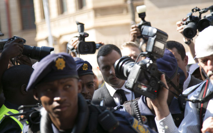 Oscar Pistorius walks the media gauntlet outside the High Court in Pretoria ahead of his sentencing on 13 October 2014. Picture: Christa Eybers/EWN.